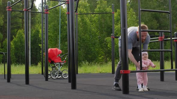 Thumbnail for Caucasian Dad Walking with Baby Daughter at Outdoor Gym