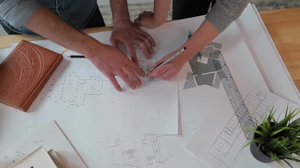 Thumbnail for Close Up Hands of Two Workers Discussing Building Drawings in Office. Closeup Shooting of Arms