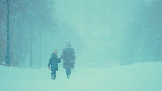 Girl and Her Mother Go on the Road to Heavy Snowfall