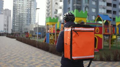 Food Delivery Courier Walking Past City Playground