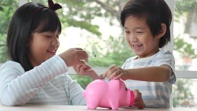 Cute Asian Child Putting A Coin Into A Piggy Bank