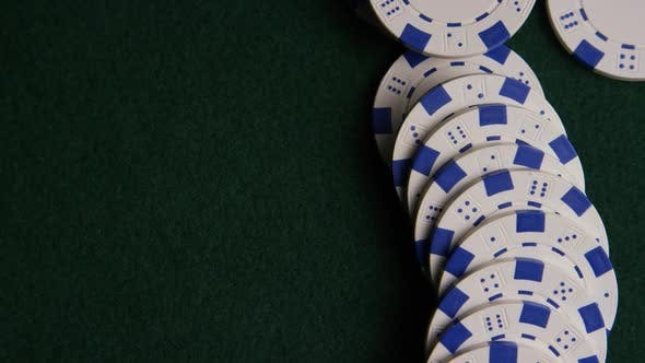 Rotating shot of poker cards and poker chips on a green felt surface - POKER 057