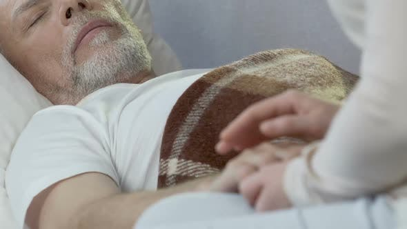 Thumbnail for Female Sitting on Edge of Bed, Holding Old Man by Hand and Taking Care of Him