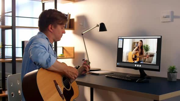 Man Learning To Play Guitar Online at Home