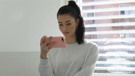 Frau schaut Smartphone-Video, weiß und pink