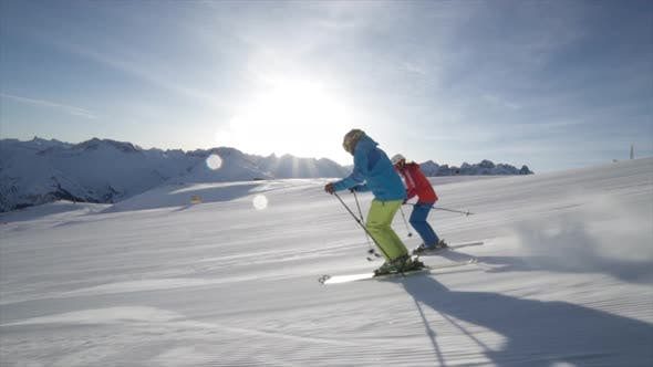 Thumbnail for A man and woman couple skiing together in the snow at a ski resort