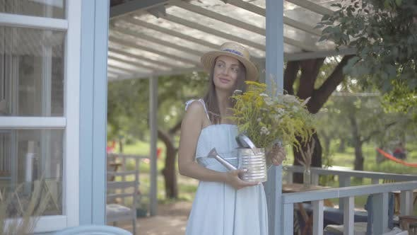 Thumbnail for Attractive Young Woman in Straw Hat and White Dress Smiling While Sniffing Wild Flowers
