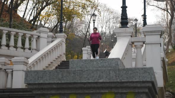 Thumbnail for Nordic walking concept. Chubby female walking up and down stairs doing intense cardio training