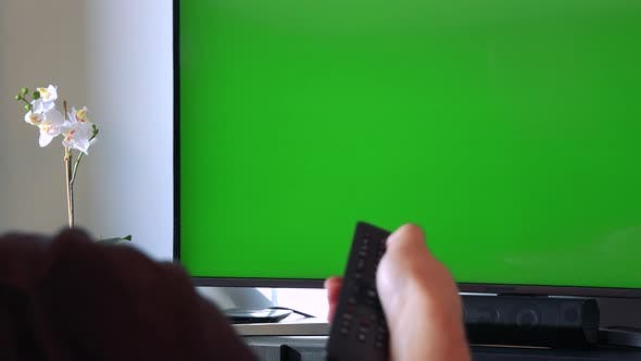 Thumbnail for A Hand Clicks with a Controller at a TV with a Green Screen