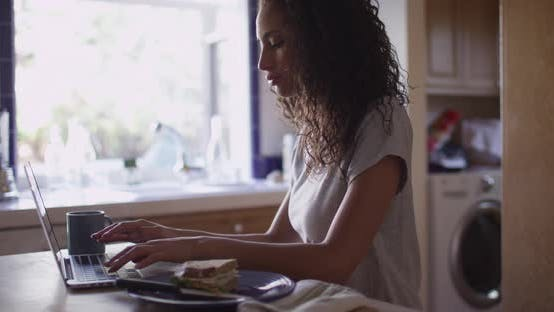 Thumbnail for Pretty hispanic woman typing on a laptop computer in kitchen