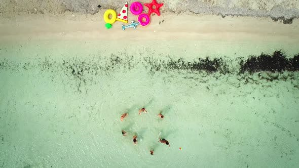 Thumbnail for Aerial view of friends playing volleyball standing in sea by sandy beach.