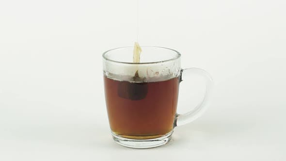 Black Tea Bag Lifting and Dropping Into Glass Transparent Mug To Brew Tea Isolated on White