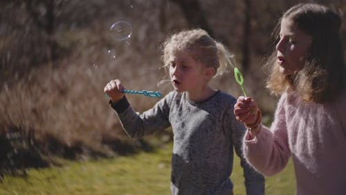 Brother And Sisters Blowing Bubbles From Bubble Wand