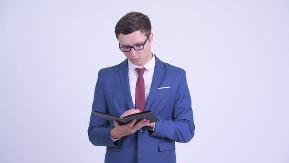 Cover Image for Young Handsome Businessman Reading Book with Eyeglasses