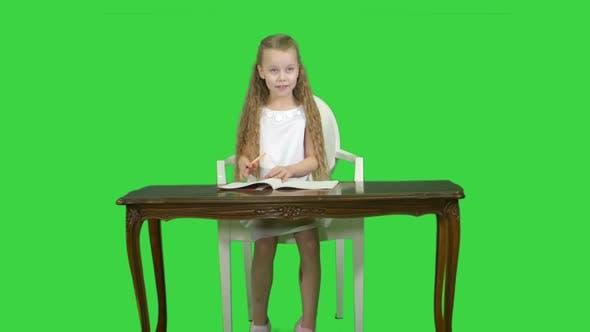 Thumbnail for Cute Little Girl Doing Homework, Writing Down on a Green Screen, Chroma Key