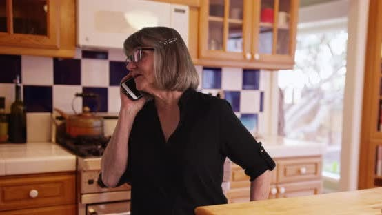 Mature white woman communicating on smartphone  in domestic kitchen setting