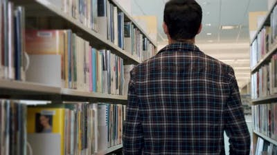 College Student Goes in the Library and Stops to Select a Book