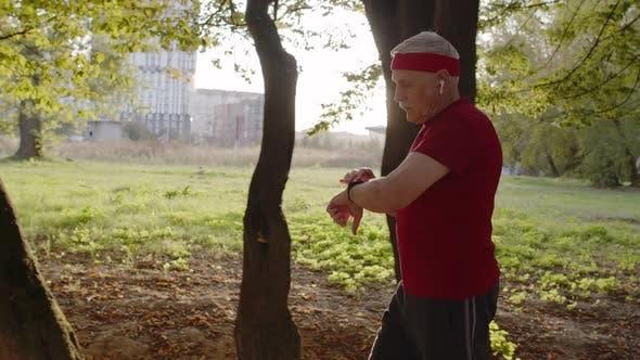 Thumbnail for Seitenansicht von Senioren Sport Runner Mann Training. Workout Cardio draußen im City Park am Morgen