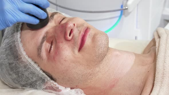 Thumbnail for Man Receiving Facial Ultrasound Cavitation Treatment By Cosmetologist