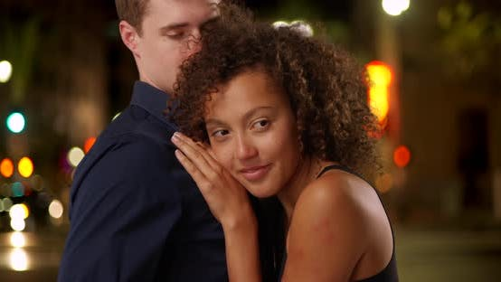 Thumbnail for Closeup portrait of mixed race couple holding each other outdoors.  Romantic couple embracing each o