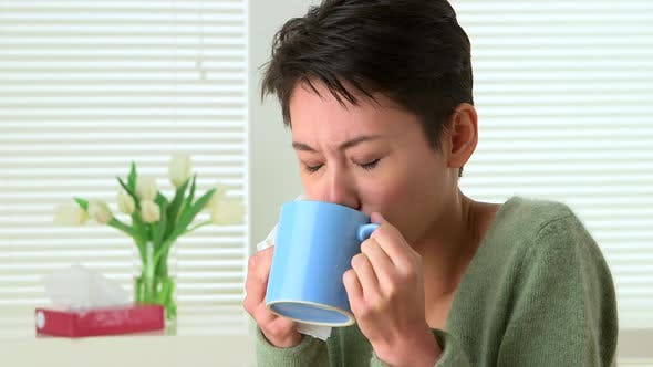 Thumbnail for Woman sick with cold sneezing and drinking tea