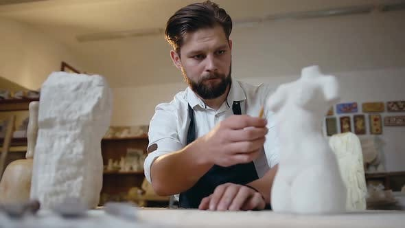 Thumbnail for Sculptor Looking at Original Sculpture Making Marks on Future Sculpture at His Workplace
