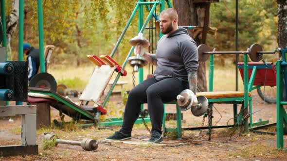 Thumbnail for A Man Bodybuilder Pulling the Dumbbells in Both Hands - the Dumbbells Chained To the Bench