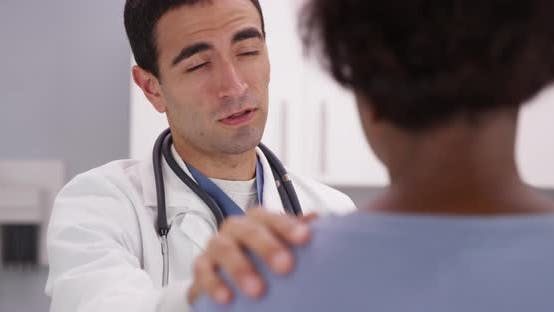 Thumbnail for Lovely male latino doctor placing hand on patients shoulder and comforting her