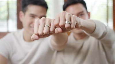 Young Asia Gay couple feeling happy showing ring at home..