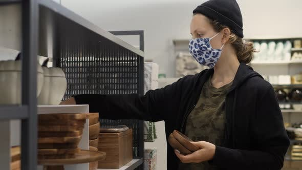Young Woman Wearing Protective Face Mask Chooses Wooden Pottery in in Dinneware Department of Home