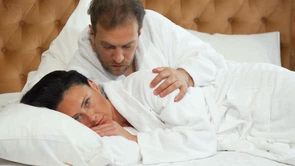 Thumbnail for Mature Woman Looking Dissapointed, Her Husband Trying Talking To Her in Bed 1080p