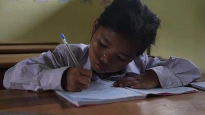 Poor Girl Writing In Classroom