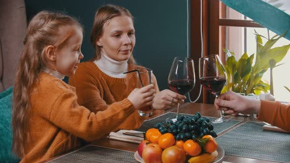 Cover Image for A Family Sitting in the Hotel Restaurant - Man and Woman Clinking Glasses and Drinking Wine