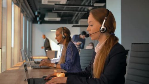 Woman Agent with Headsets Working in a Call Centre.