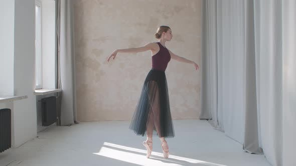 Professional Performance of a Fragile Ballerina Against the Background of Large Panoramic Windows