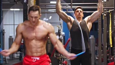Two Men Training in the Gym  Training Hands and Jumping Over the Rope