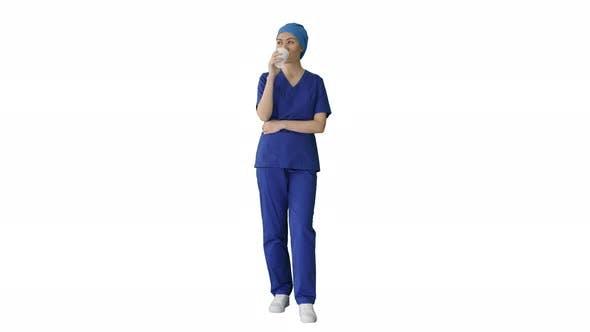Smiling Female Doctor or Nurse in Blue Uniform Having a Coffee Break on White Background.