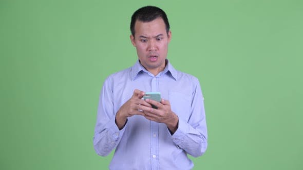 Cover Image for Stressed Asian Businessman Using Phone and Getting Bad News