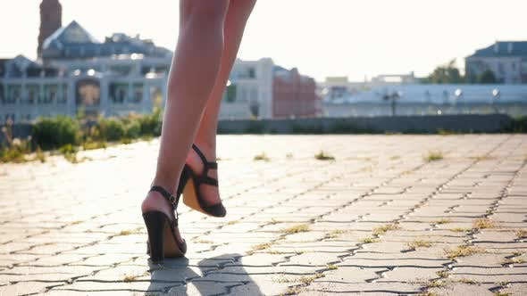 Attractive Mulatto Young Woman Starts Walking Forward on High Heels - Runs Her Hands Over Her Butt