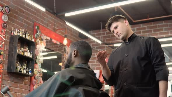 Hairdresser Cuts the Client's Hair with Scissors