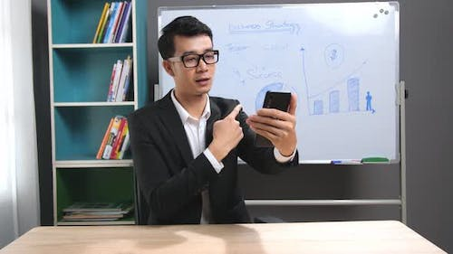 Asian Business Man Making Face time Video Calling With Smartphone At Home