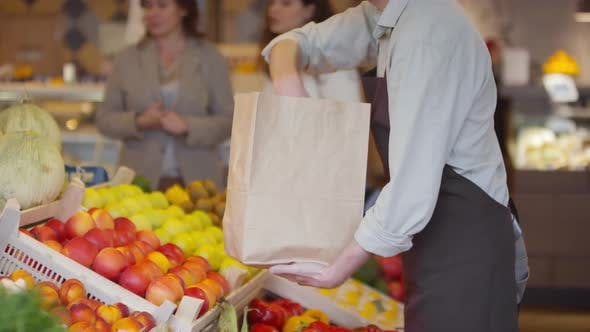 Thumbnail for Seller Packing Apples into Craft Paper Bag for Female Customers