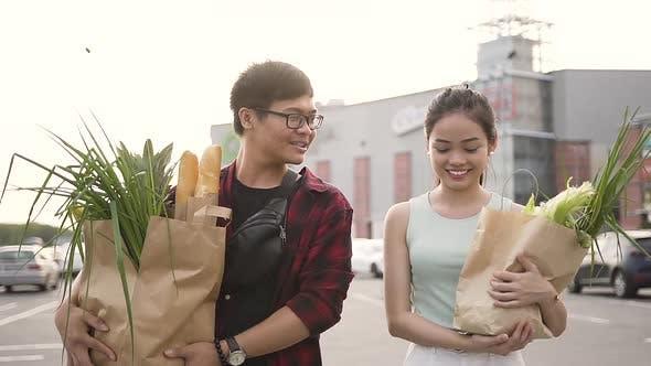 Thumbnail for Fröhlich asiatische Mann und Frau halten Big Food Taschen in der Nähe der Supermarkt