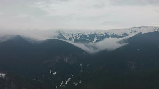 Aerial Top View Over Cloudy Rocky Snowy Mountain with clouds.Italian Alps Mountains with Wild Windy
