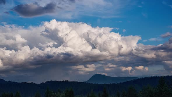Big cumulus cloudsover forest landscap. A rainbow is being formed 4K