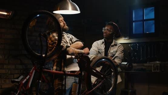 Two Men Talking in a Bicycle Repair Shop