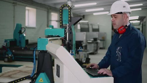 A Factory Worker is Standing at the Control Panel