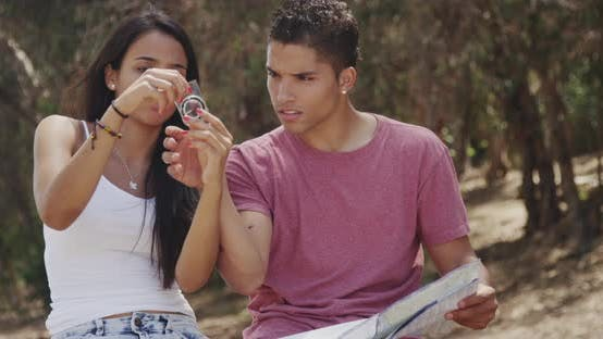 Hispanic couple trying to use map and compass