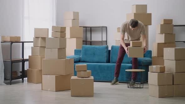 Junger Mann bewegt sich in Pappkartons