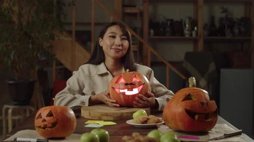 Girl Sitting at the Dinner Table and Holding a Pumpkin for Halloween
